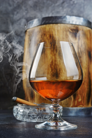 Strong alcoholic drink cognac in sniffer glass with smoking cigar in crystal ashtray and vintage wooden barrel on gray concrete background