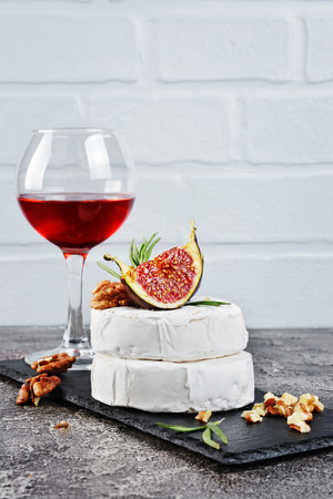 Gourmet appetizer of white brie cheese or camembert with fresh figs, nuts and glass of red wine on slate board and gray concrete background