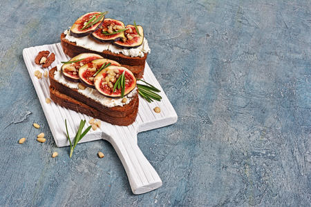 Vegetarian sandwich with figs, soft cheese, honey, nut and rosemary on white wooden cutting board and blue concrete background with copy space Stock Photo