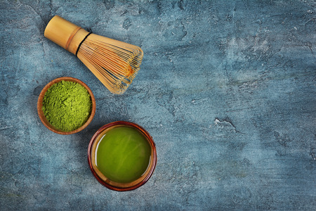 Top view on organic green matcha tea powder in bowls with bamboo whisk on blue concrete background with copy space Reklamní fotografie
