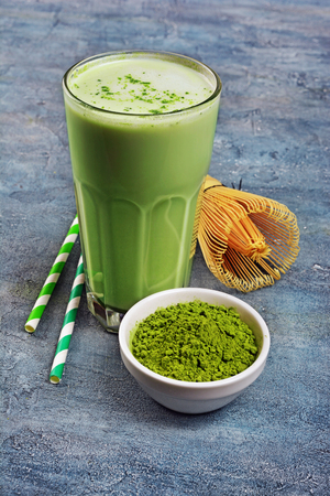 Organic green matcha tea latte in glass and powder in white bowl with bamboo whisk and cocktail straw on blue concrete background