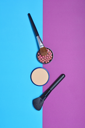 Top view on set of beauty products: decorative cosmetics as balls and compact powder and makeup brushes on bright blue and purple background 写真素材
