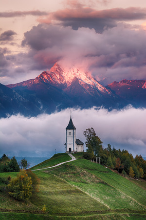 Beautiful sunrise landscape of church Jamnik in Slovenia on green hill with blue cloudy sky and mountains background Foto de archivo