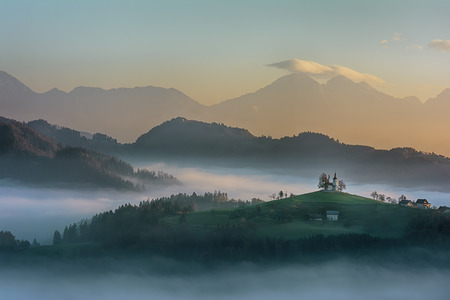 Beautiful sunrise landscape of Saint Thomas Church in Slovenia on hilltop in the morning fog with blue and orange sky and Triglav mountain background