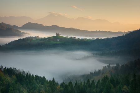 Beautiful sunrise landscape of Saint Thomas Church in Slovenia on hilltop in the morning fog with pink and orange sky and Triglav mountain background