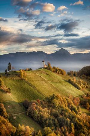 Mooi zonsopganglandschap van kerk Jamnik in Slovenië op groene heuvel met blauwe bewolkte hemel en bergenachtergrond Stockfoto