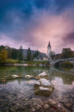Beautiful sunrise landscape of lake Bohinj, Triglav National Park, Julian Alps in Slovenia with church and arch bridge on blue cloudy sky background