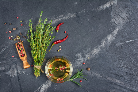 Aromatic or flavored olive oil in glass bowl with spices and herbs as chili peppers and thyme on black marble background with copy space