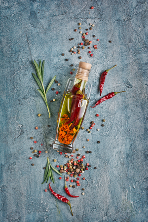 Aromatic or flavored olive oil in glass bottle with spices and herbs as chili peppers and rosemary on blue concrete background