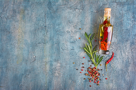 Aromatic or flavored olive oil in glass bottle with spices and herbs as chili peppers and rosemary on blue concrete background with copy space 免版税图像