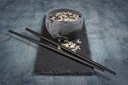 Gray handcrafted pottery bowl of mix uncooked black and brown rice with wooden chinese chopsticks on slate board and blue concrete background