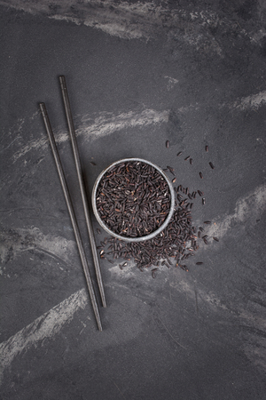 Top view of uncooked black rice in gray bowl with wooden chinese chopsticks on dark marble background