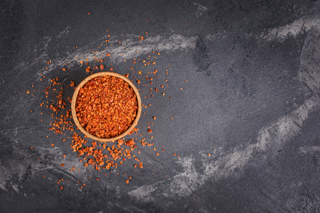 Top view of crushed dry red hot chili pepper in wooden bowl on black marble background with copy space