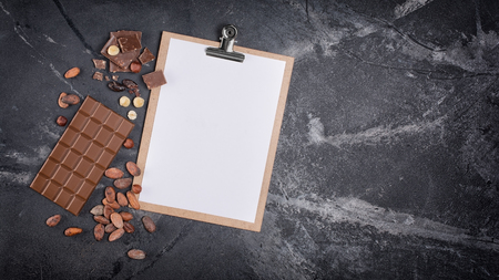 Top view of mockup composition with blank white sheet of paper with chocolate on black marble background with copy space