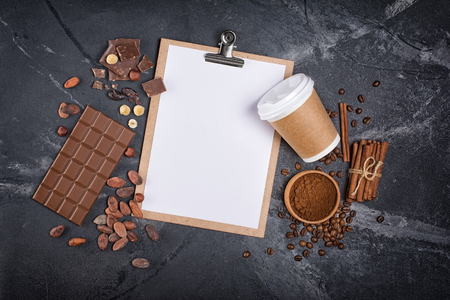 Top view of mockup blank white sheet of paper and disposable take-out coffee cup with chocolate and spices on black marble background with copy space