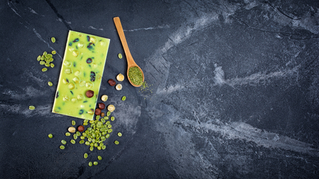 Top view of tasty green chocolate bar with whole hazelnuts and coffee beans on black marble background with copy space 스톡 콘텐츠