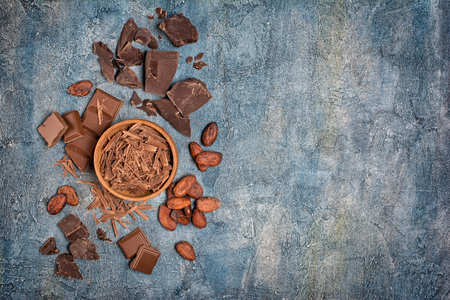 Top view of chocolate chips in wooden bowl with pieces of chocolate bar and cocoa beans on blue concrete background with copy space
