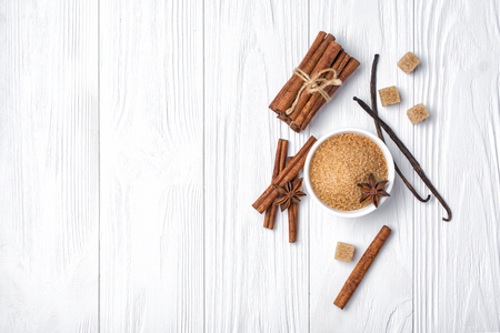 Top view of brown cinnamon granulated and cane cubes sugar with different spices for confectionery on white wooden background with copy space