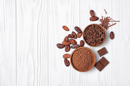 Top view on tasty chocolate bars with cocoa beans and bowl of chocolate chips and cacao powder as ingredients for confectionery on white wooden background with copy space Stock Photo