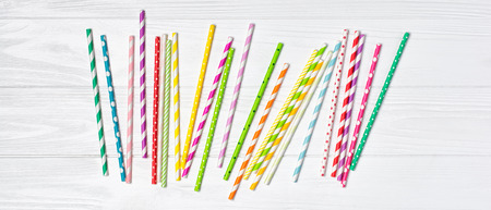 Top view of bright striped green, yellow, pink and purple cocktail straws as attributes of party on white wooden background 版權商用圖片