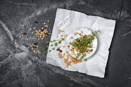 Top view on gourmet appetizer of white brie cheese or camembert with kitchen herbs and nuts on black marble background with copy space