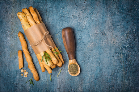 Top view of traditional Italian appetizer grissini on white wooden board with rosemary spice in rustic spoon on blue concrete background with copy space