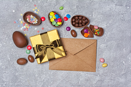 Top view on chocolate traditional Easter eggs and golden gift box with kraft envelope and bright colorful dragee, sugar sprinkles on gray concrete background