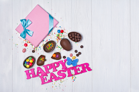 Top view on pink text of happy Easter and gift box with chocolate traditional eggs and bright colorful dragee on white wooden background