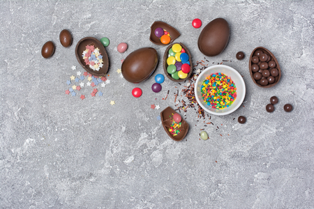 Top view on chocolate traditional Easter eggs with bright colorful dragee and sugar sprinkles or confetti on gray concrete background with copy space