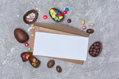 Top view on mockup of blank white card and kraft envelope with chocolate traditional Easter eggs and bright colorful dragee or confetti on gray concrete background Stockfoto