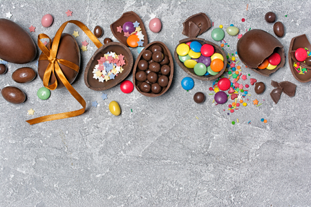 Top view on chocolate traditional easter eggs with bright colorful dragee and sugar sprinkles or confetti on gray concrete background with copy space Stock Photo