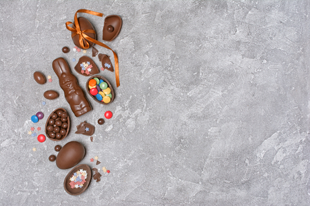 Top view on chocolate traditional easter eggs and bunny with bright colorful dragee and sugar sprinkles or confetti on gray concrete background with copy space 写真素材