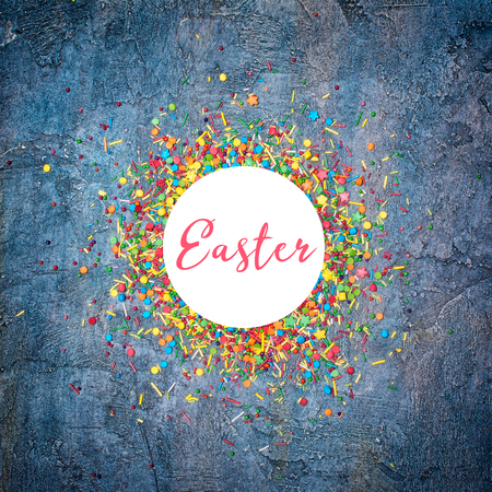 Easter template frame for text with colorful sugar sprinkles or confetti on blue concrete background Imagens - 116524848