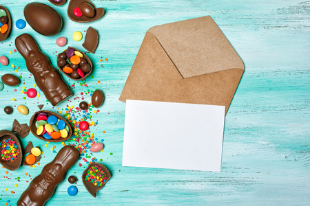 Top view on mockup of blank white card in kraft envelope with easter chocolate eggs and bunnies on green wooden background
