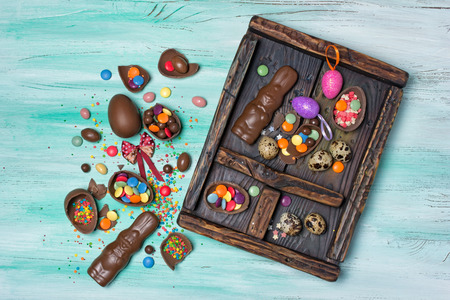 Top view on easter chocolate traditional eggs, bunnies and sugar sprinkles or confetti in vintage wood box on green wooden background