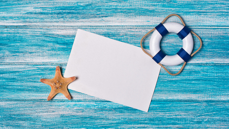 Top view on mock-up of white paper card for photo or lettering with starfish and lifebuoy on blue wooden background with copy space Stock Photo