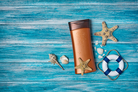 Top view on bronze bottle with sunscreen and seashells as concept of vacation time on blue wooden background with copy space 스톡 콘텐츠