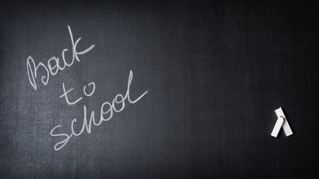 Inscription back to school on black chalk board background with copy space