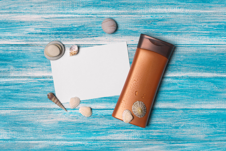 Top view on mock-up of white paper card with bottle of sunscreen and sea stones on blue wooden background Imagens