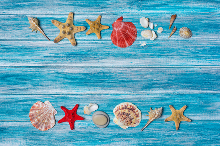 Top view on starfish and seashells on blue wooden background as concept of vacation time with copy space