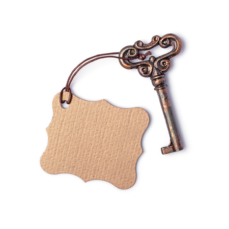 Concept of new life, dream or house with vintage key and mock up clean cardboard figured tag isolated on white background 版權商用圖片