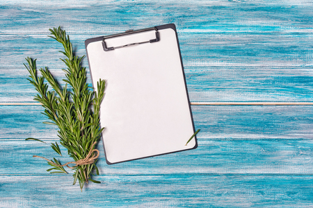 Concept of meal plan on clipboard with fresh rosemary spice on blue wooden background with copy space