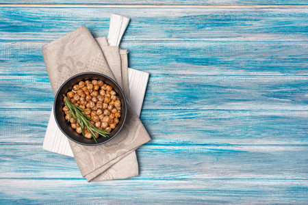 Roasted salty and spicy chickpeas in black bowl with rosemary on white board with linen napkin and blue wooden background with copy space