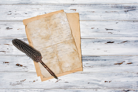 Mockup of empty old vintage yellowed paper sheets with luxury quill pen on white wooden background with copy space Foto de archivo