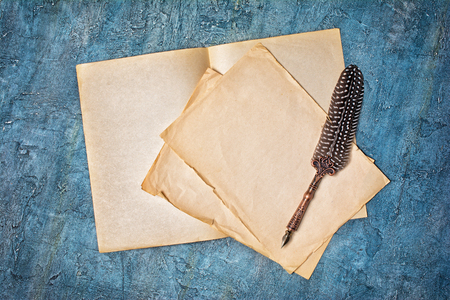 Mockup of empty old vintage yellowed paper sheets with luxury quill pen on blue concrete background