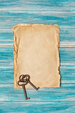 Mockup of empty old vintage paper sheets with retro keys on blue wooden background Imagens