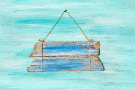 Vintage blue signboard for information hanging by rope on rustic turquoise wooden background Banco de Imagens