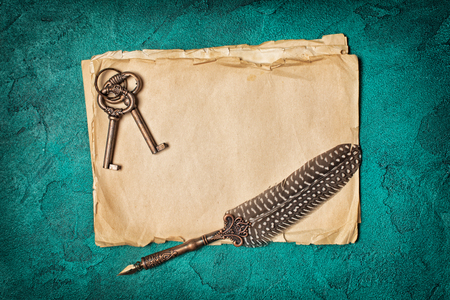 Vintage composition of yellowed paper sheets with luxury quill pen and retro keys on turquoise concrete background