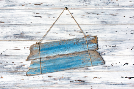 Vintage blue signboard for information hanging by rope on rustic white wooden background