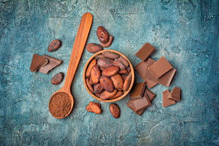 Flatlay of chocolate bar with cocoa beans and powder for confectionery on blue concrete background Reklamní fotografie - 121994717